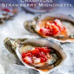 close up of an oyster with chopped strawberries, with a blue shadow with writing in it at the top