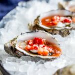 sq picture showing the raw oyster on a bed of ice and the mignonette sauce dripping onto the ice