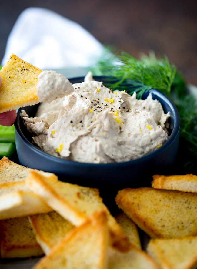 blue bowl of smoked fish dip with toast points arranged around and one being dipped in.