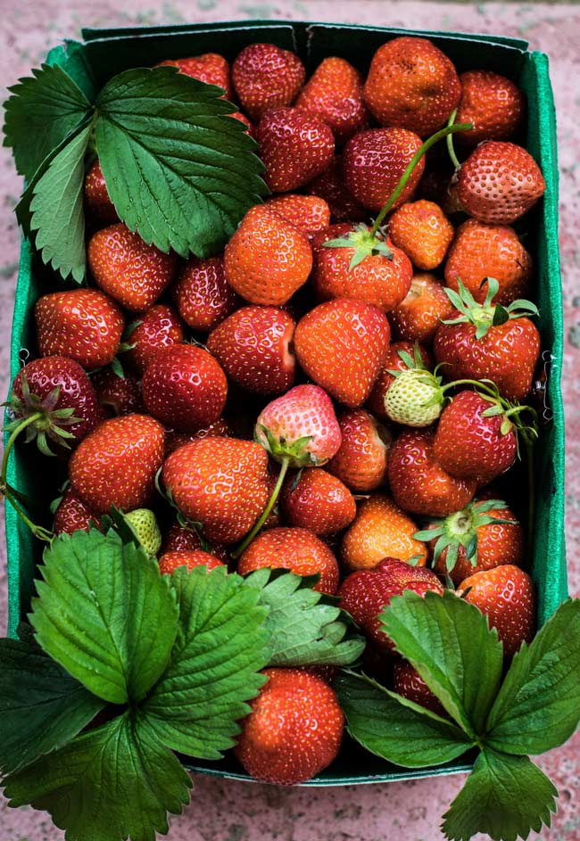 green cardboard basket full of fresh strawberries and their leaves