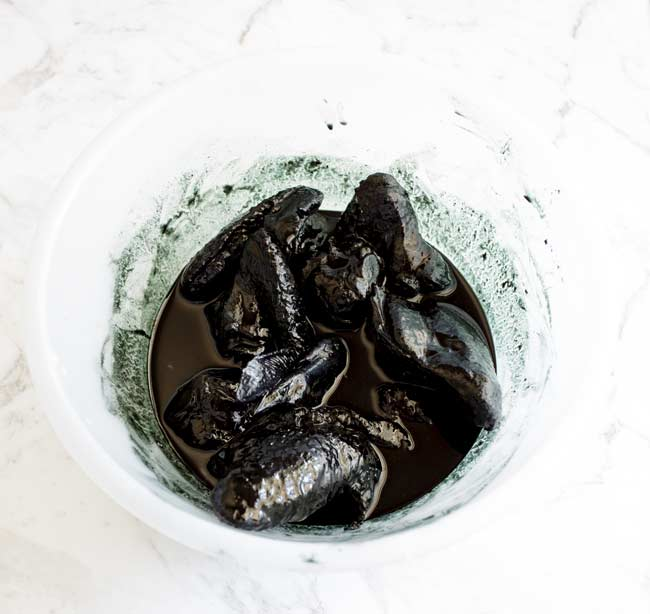 plastic bowl full of a black green marinade and chicken wings