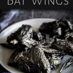 grey plate of black chicken wings with text at the top