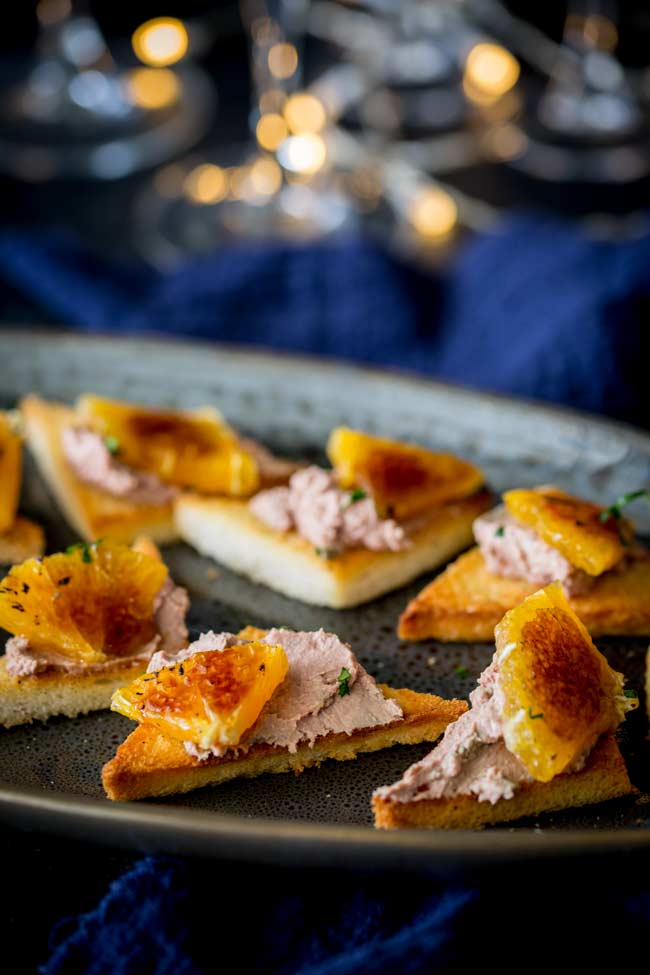 an oval plate with toast points spread with pate and garnished with parsley and caramelized orange pieces with fairy lights in the background