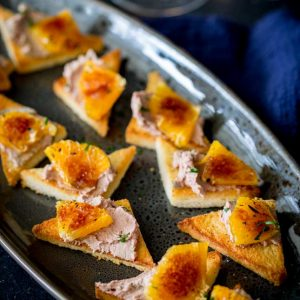sq image from overhead showing the whole platter of toast and pate with caramelize orange