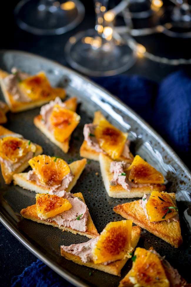 a grey speckled plate with toast points spread with pate and garnished with parsley and caramelized orange pieces