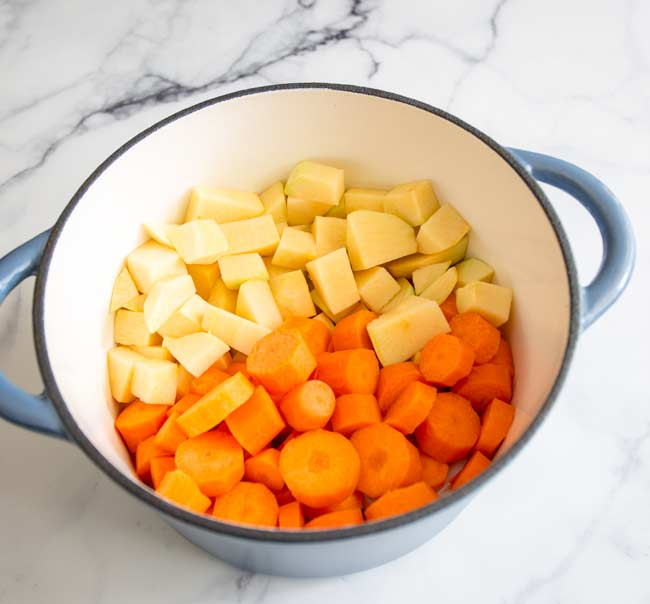 chopped rutabaga and carrot in a cast iron dutch oven