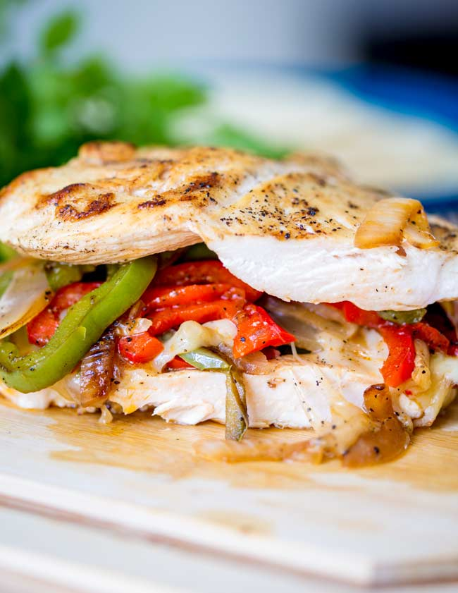 A cut away section of 2 chicken breasts sandwiched towgetrh with cheese and peppers
