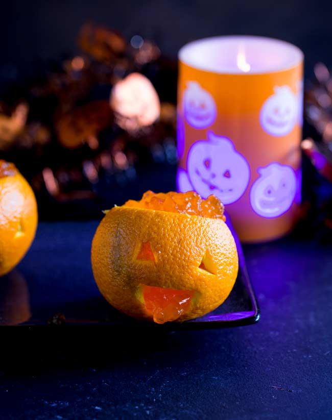 orange jack-o-lantern with jelly inside, with a halloween candle in the background