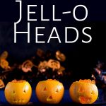 3 jello filled orange jack-o-lanterns, on a blue plate with text at the top