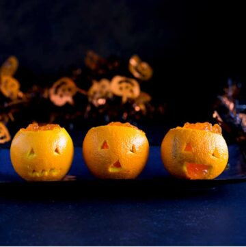 3 jack o lantern oranges sat on a blue plate on a dark table with halloween tinsel behind them