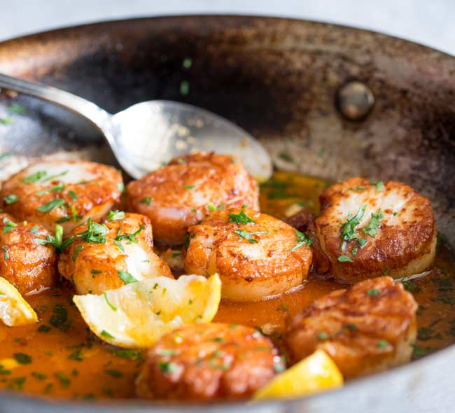 a large metal fry pan with a melted paprika butter in it, dotted with seared scallops and wedges of lemon