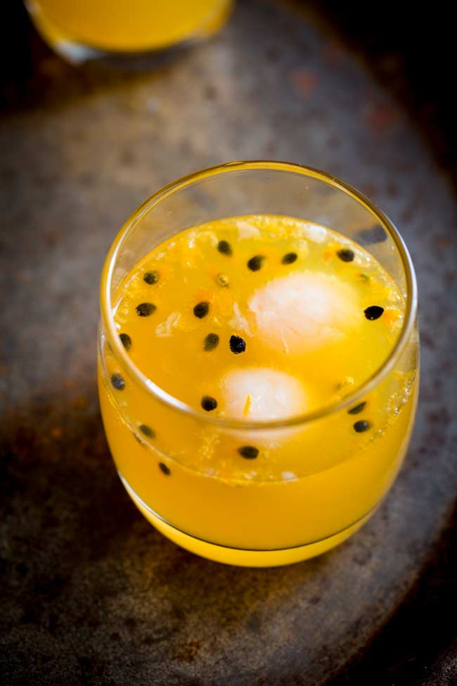 overhead looking down into a glass of orange liquid with passionfruit and lychee floating in it