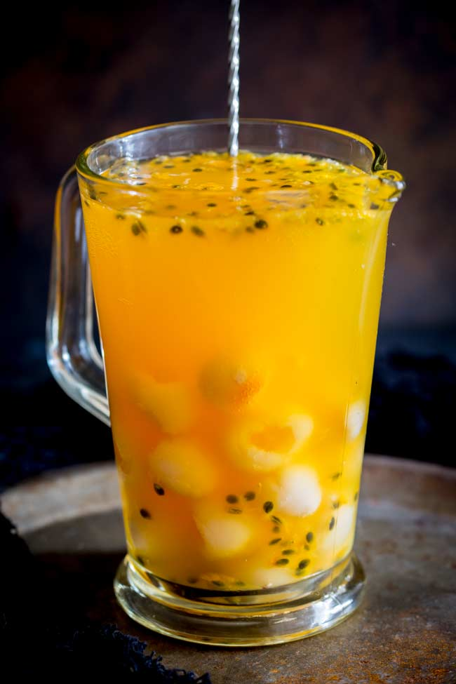 large glass jug with a metal spoon in it filled with an orange drink and garnished with passionfruit and lychee