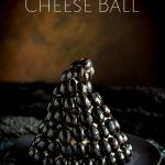 rusty back drop with a black olives crusted witches hat cheese ball on a black plate.