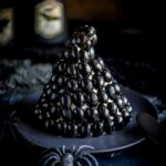 close up on the witches hat cheese ball with a plastic spider crawling onto the plate