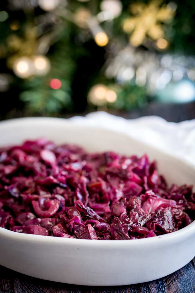 head on shot showing the top of the braised cabbage dish with fairy lights and a christmas tree in the background