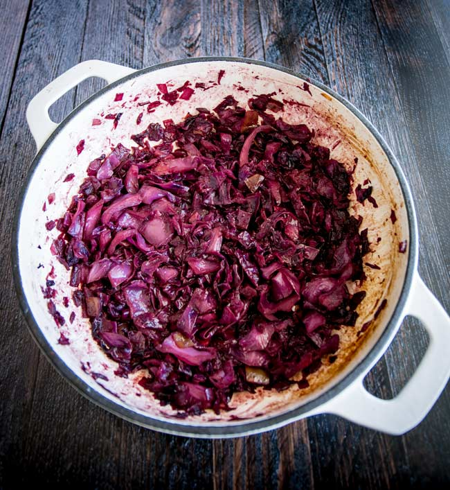 overhead of a large cast iron pan filled with braised red cabbage
