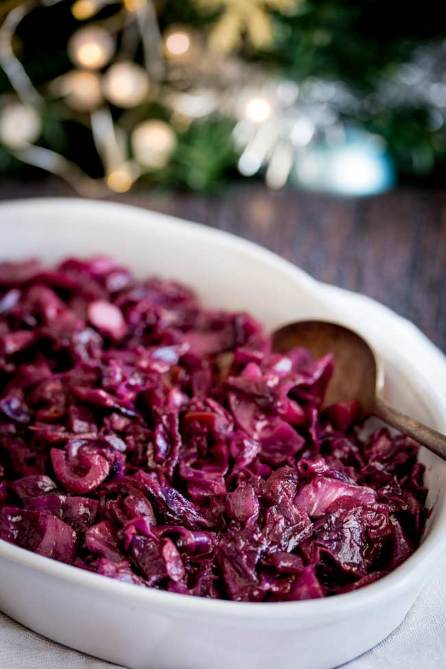 braised red cabbage in an oval serving dish on a wooden table with a christmas tree in the background