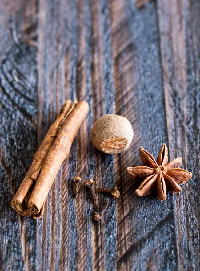 cinnamon stick, star anise, 4 cloves and a nutmeg on a wooden table