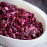 Close up on the chunky braised red cabbage in an oval serving dish on a wooden table