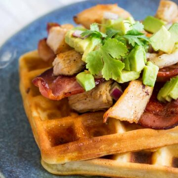 Square image showing a close up of the turkey, bacon and avocado topping on the waffles