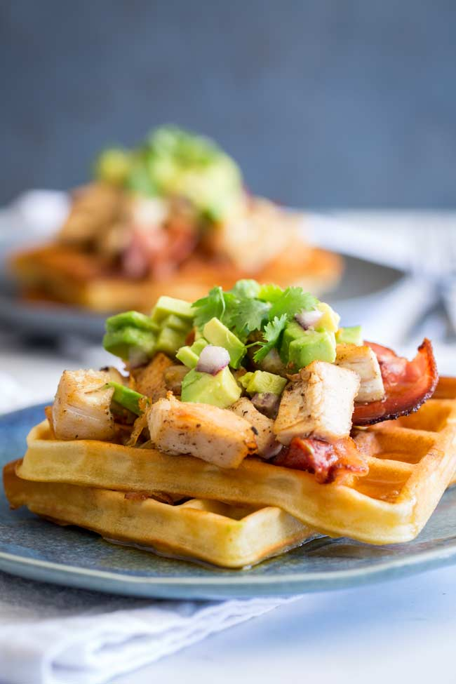 a blue plate of turkey waffles with a second plate in the background