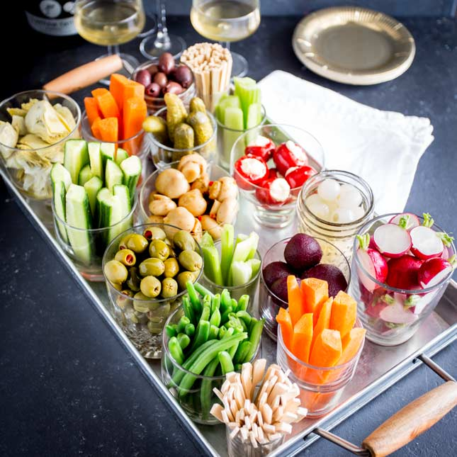 square picture showing different glasses, filled with pickles, on a metal tray