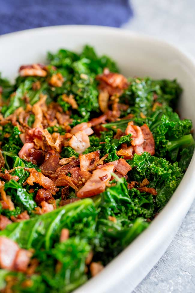 Slight overhead photo showing the bright green kale dressed with crispy bacon