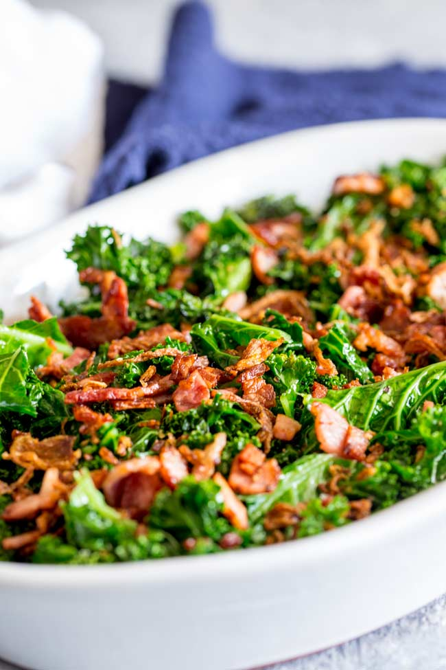 White oval serving dish filled with sautéed kale and bacon