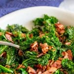White bowl of sautéed kale with bacon, with text at the top