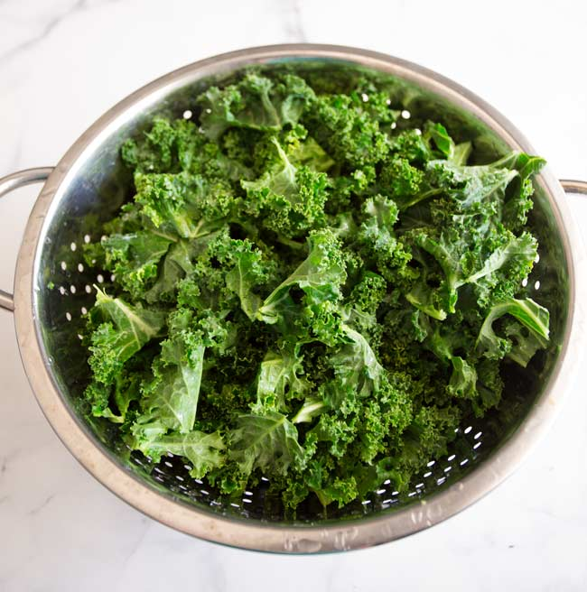 chopped raw kale in a silver colander on a marble work surface