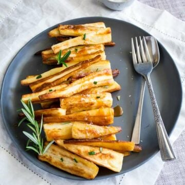 sq picture showing a grey plate with parsnips line up on it with a drizzle of caramel sauce and sprigs of rosemary