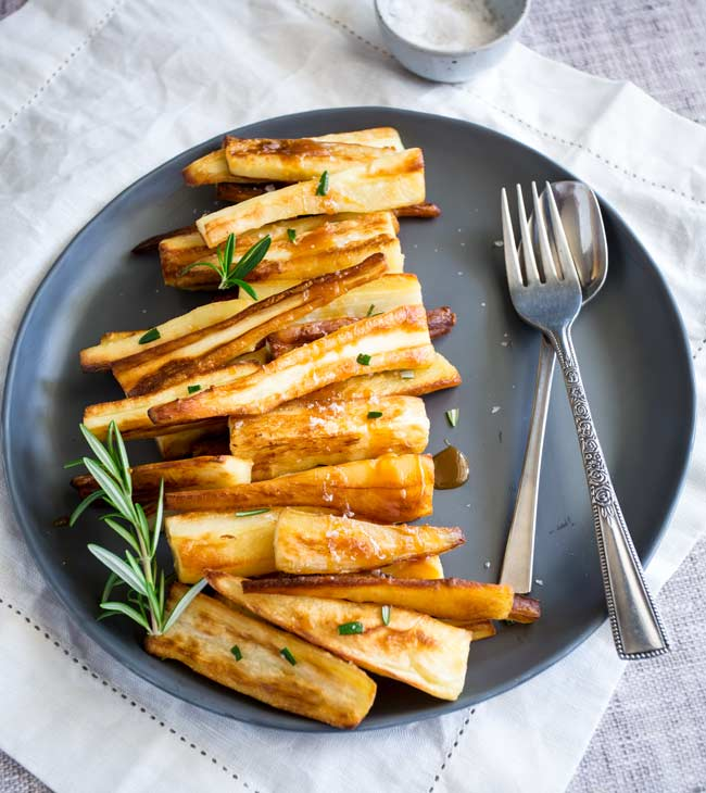 overhead view of a grey plate with roasted parsnips down one side and a fork on the other.