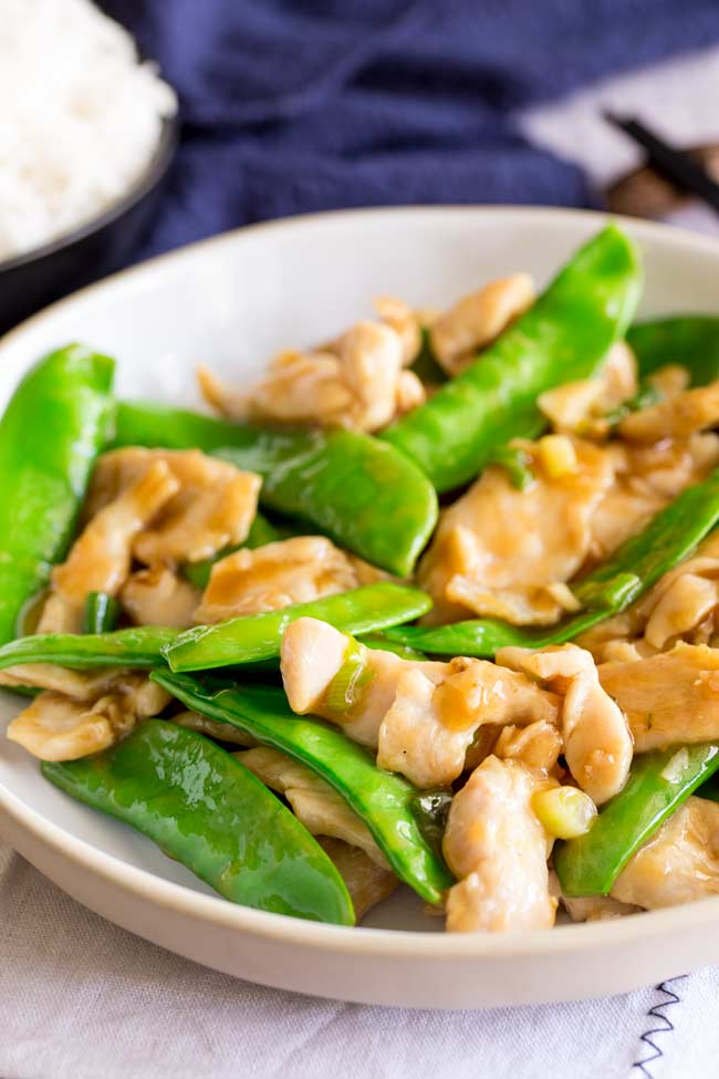 Deep white plate with stir fried chicken and snow peas in it
