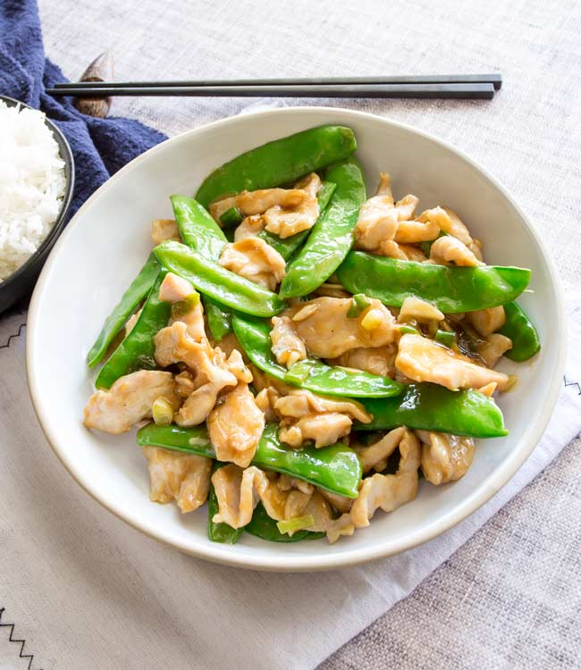 Overhead shot of chicken and snow peas in a white bowl on a beige table with a blue napkin and black chopsticks