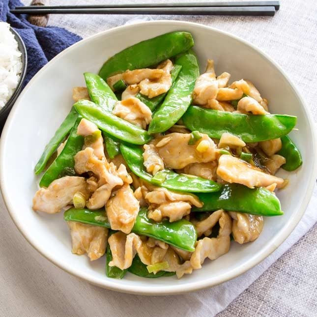 takeout style chicken and snow pea stir fry in a white bowl with a bowl of rice and chopsticks
