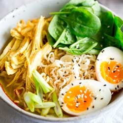 small square photo with a close up on ramen noodles in a bowl of broth with shredded turkey, egg and spinach