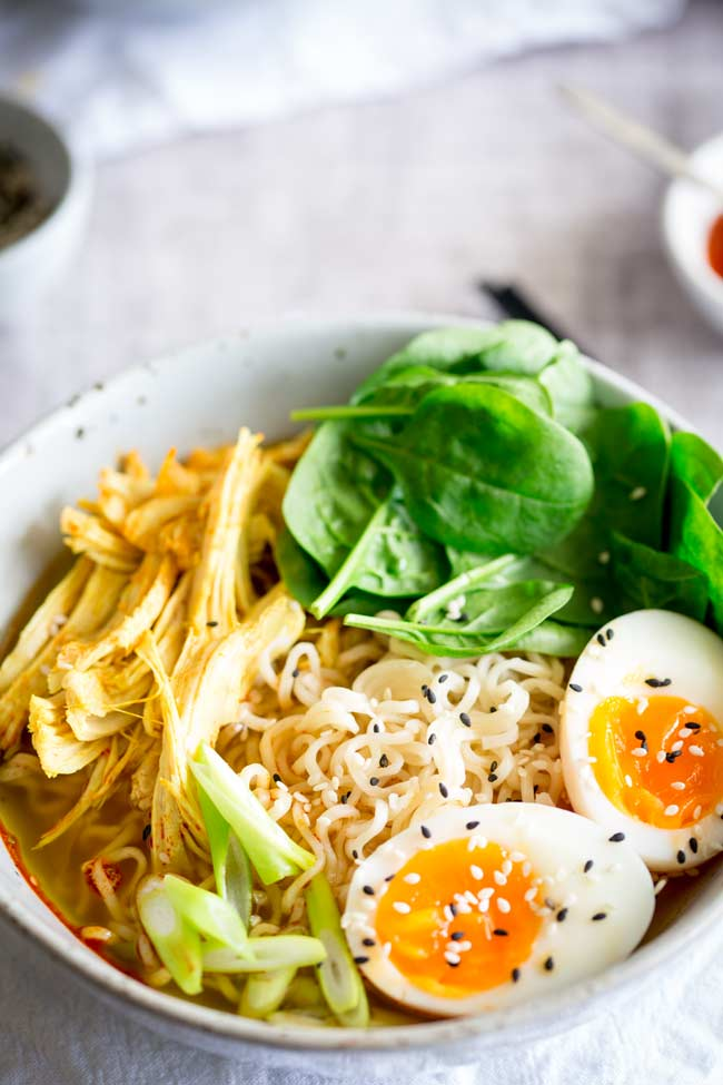 overhead view of a rustic bowl filled with noodles, shredded turkey, egg and spinach