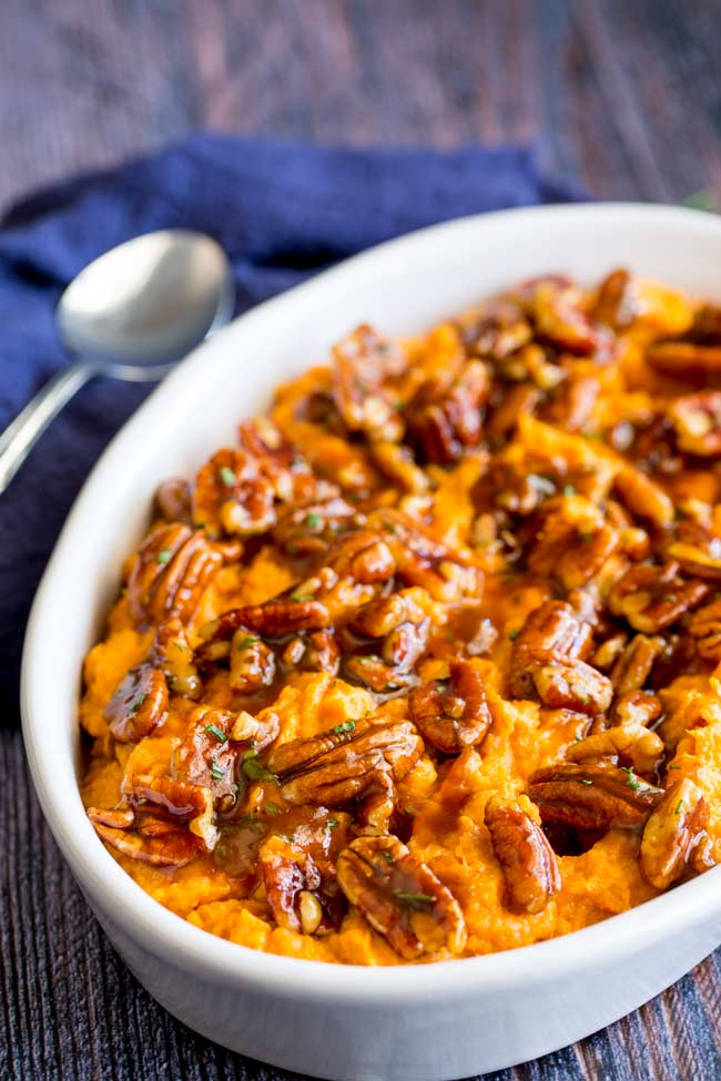 Sweet potato mash in a white oval serving dish on a wooden table with a spoon in the background