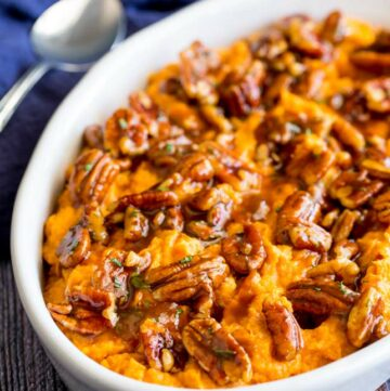 oval dish filled with sweet potato mash topped with pecans and maple syrup