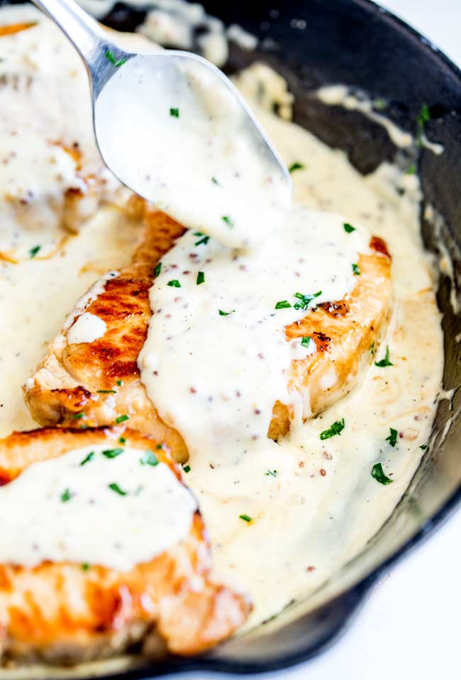 creamy honey mustard sauce being drizzled over a pork chop with a silver spoon