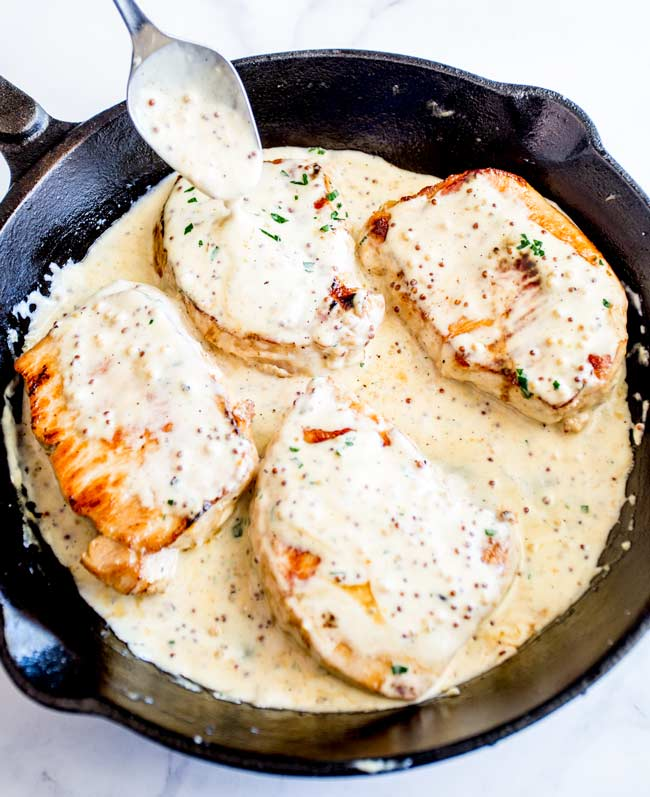 4 boneless pork chops in a cast iron skillet with a creamy sauce being drizzled over them