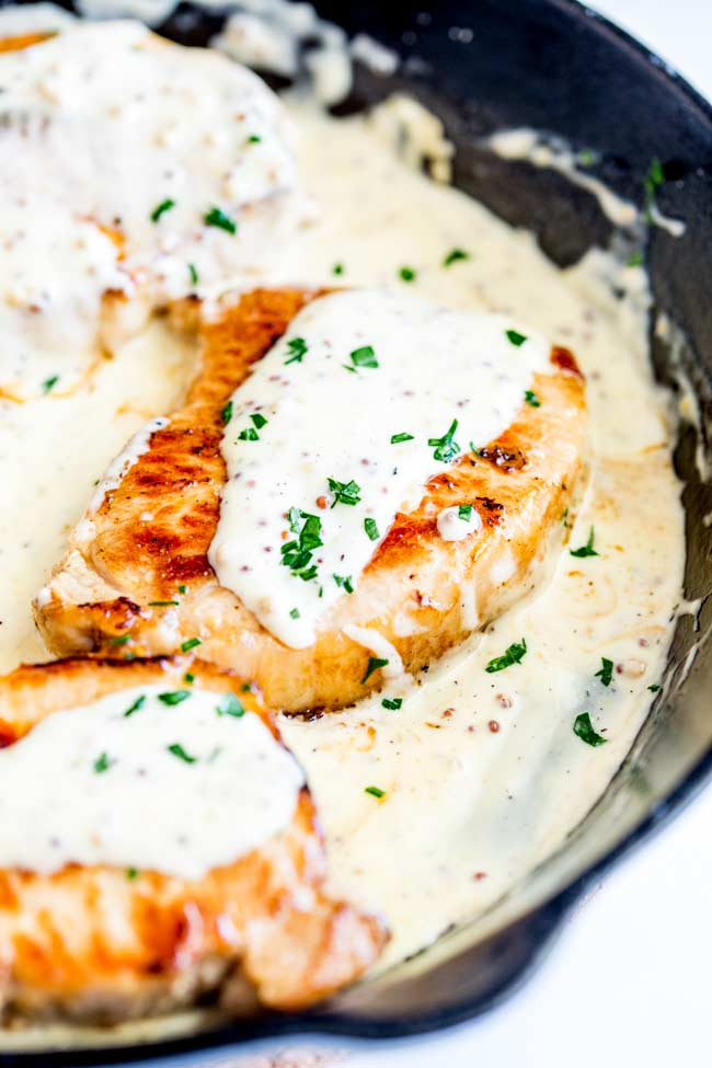 close up on one pork chop in a cast iron pan with a creamy sauce around it