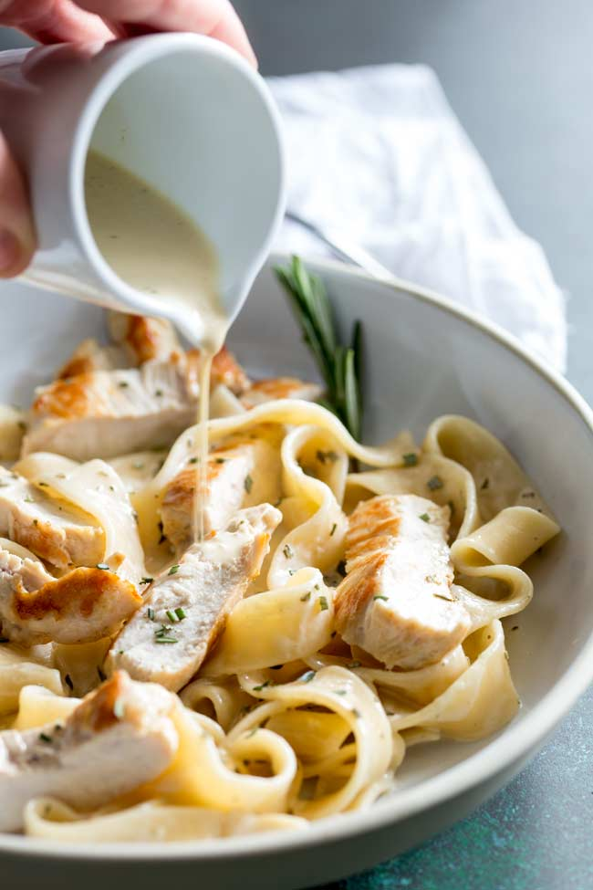 creamy rosemary sauce in a small white jug being poured over chicken pasta