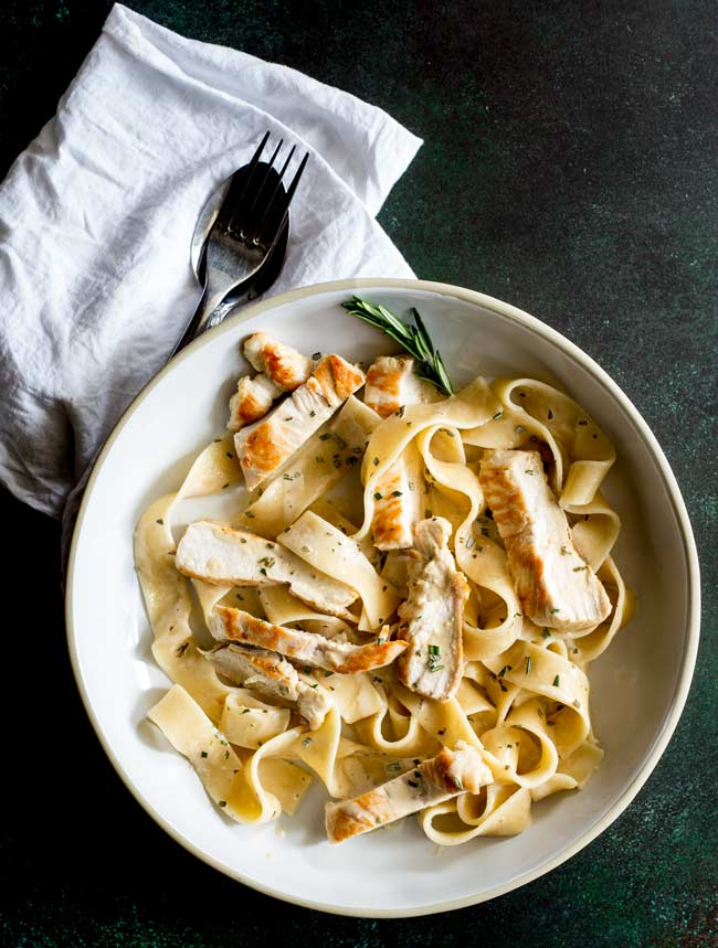 overhead view of a large rustic white bowl of creamy chicken pasta on a dark green table with a white napkin