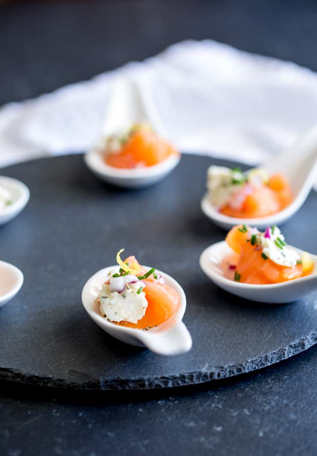 6 smoked salmon and cream cheese amuse spoons on a circular slate mat.