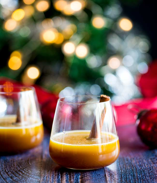 Two glassed of hot buttered bourbon on a wooden table with a Christmas tree in the background