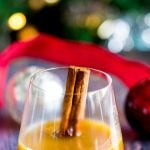single glass of hot buttered bourbon with christmas decorations behind and text overlaid