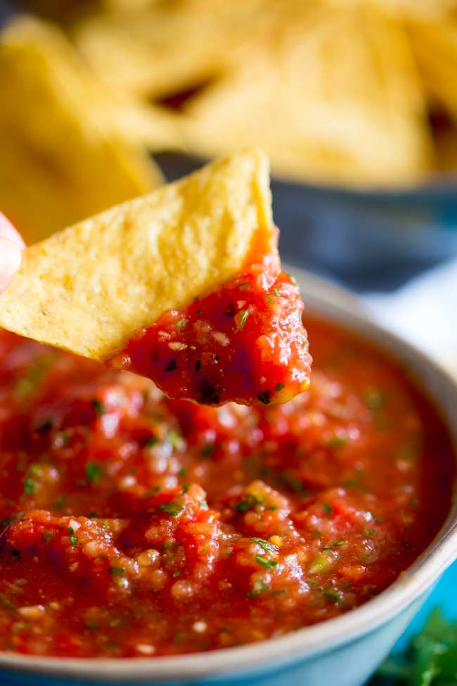 corn chip being dipped into a fresh homemade salsa
