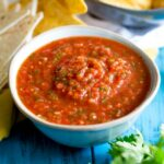close up on the homage salsa in a small white bowl with chips behind it
